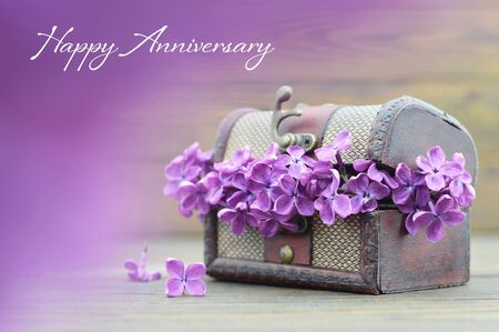 Anniversary card with violet lilac flowers in wooden chest