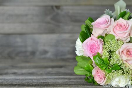 Bouquet of flowers on wooden background with copy space