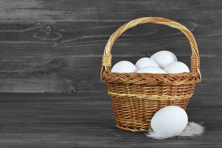 Chicken eggs in basket on wooden background