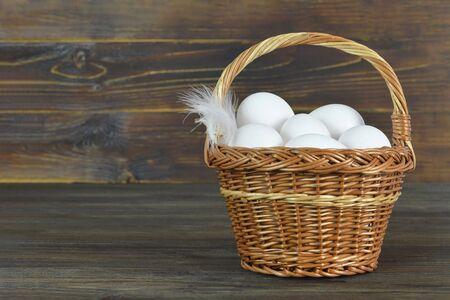 White chicken eggs in basket on wooden background