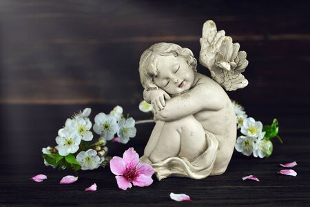 Guardian angel and spring flowers on dark wooden background
