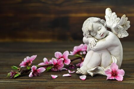 Guardian angel and spring flowers on wooden background