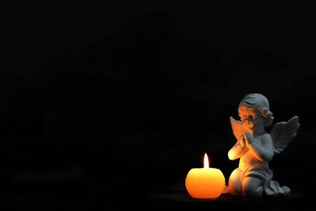 Angel and burning candle on black background