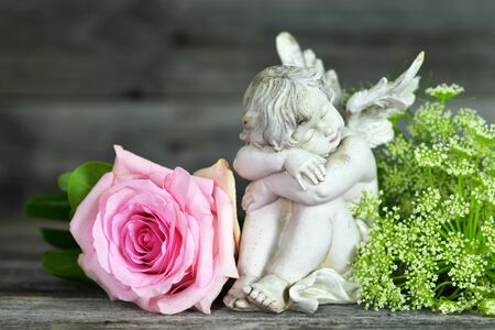 Guardian angel and pink rose on wooden background