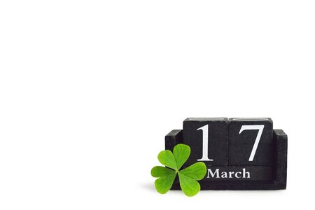 St Patricks Day background. Wooden vintage calendar and lucky clover isolated on white background