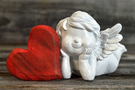 Angel and heart on wooden background. Valentines Day concept