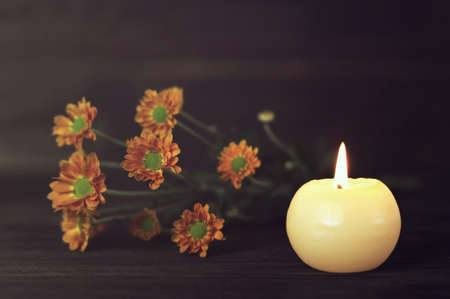 Candle and chrysanthemum flowers on wooden background