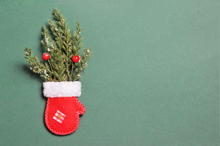 Christmas card with red Christmas mitten and fir branches on green background