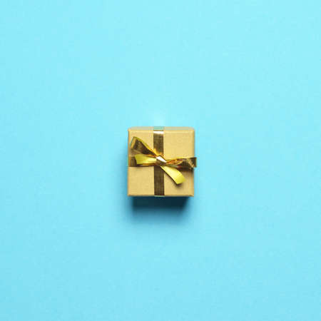 Christmas gift with golden ribbon on pastel blue background