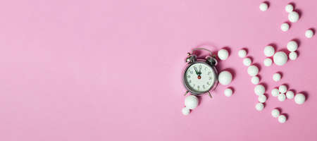 New Year midnight clock and white glitter ball decorations on pink background with copy space Banco de Imagens
