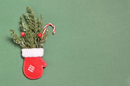 Red Christmas mitten and fir branches on green background with copy space Zdjęcie Seryjne