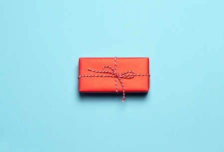 Christmas gift on blue background. Minimal flat lay Christmas composition