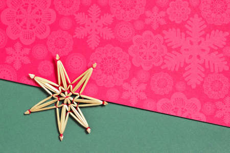 Christmas straw snowflake decoration on red and green background