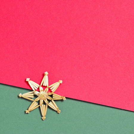 Christmas straw snowflake decoration on red and green background. Minimalistic Christmas concept
