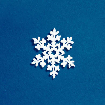 Christmas snowflake decoration on blue background. Minimalistic Christmas concept