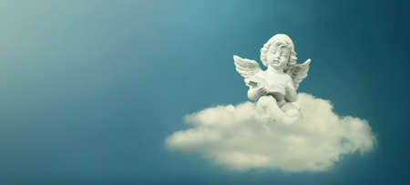 Little angel sitting on the cloud and reading book