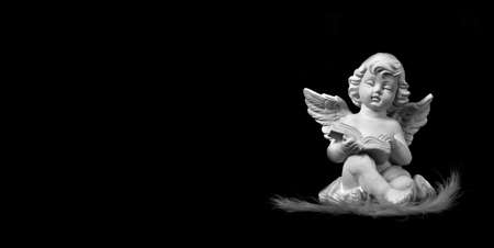 Angel sitting and reading book isolated on black background Imagens