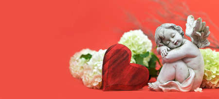 Sleeping angel, red heart and flowers on red background with copy space