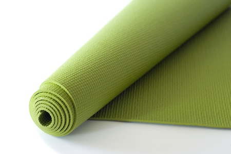 A green yogapilatesexercise mat rolled up on white.  Stock Photo