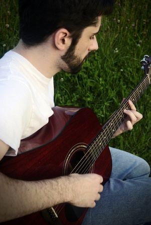 overtone: A man playing a red wood acoustic guitar in the grass. Image is done in a dark style with high contrast and a bit of a sepia overtone.