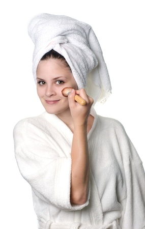 regimen: A young woman in white towel and robe applying makeup after a shower.