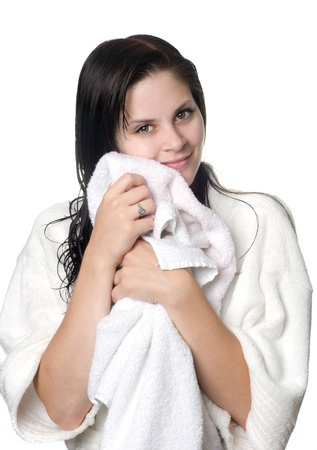 toweling: A young woman with wet hair in white robe toweling off after a shower.
