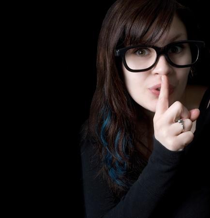 Una niña comprarle con gafas goofy sobre fondo negro de señalización para tranquilo con su dedo en la boca. Foto de archivo - 8598078