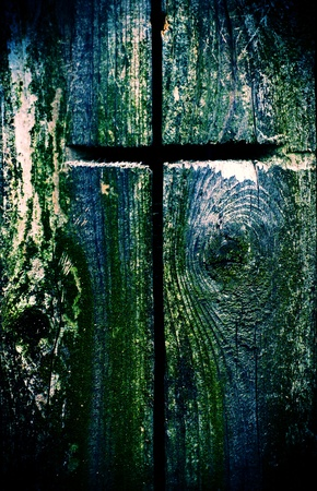 cross processed: A cross carved into old wood in a cross processed style.