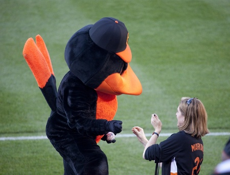 BALTIMORE - April 30: The Orioles team mascot, the Oriole Bird, signs a baseball for an Orioles fan before the game at Camden Yards on April 30, 2010 in Baltimore, Maryland.