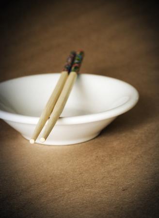 Chopsticks on a small white bowl photo