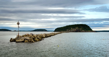 breakwater: Breakwater wall in Bar Harbor, Maine in the United States with a small island at the far end  Stock Photo
