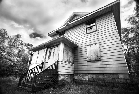A boarded up, broken down, abandoned, haunted house in black and white.