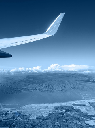 Aerial view from the window of an airplane of a populated area merging with a mountain range.