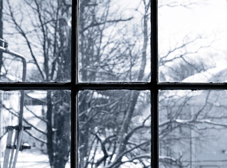 A winter scene of trees through a dirty window. Stock Photo