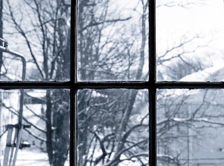 Een winters tafereel van bomen door een vies raam. Stockfoto