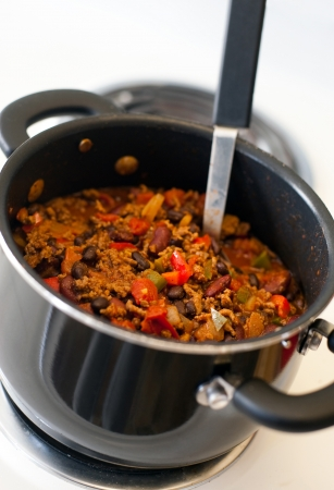 stove: A pot of chili cooking on a white stove. Stock Photo