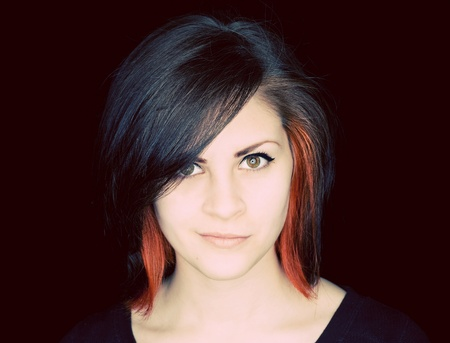 A young woman with funky hair in black and red-orange on a black background.  Stock Photo