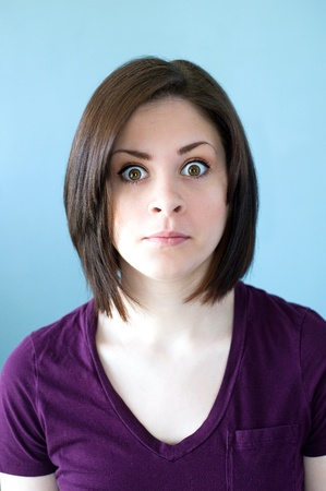 A portrait of a shocked young woman with wide eyes.
