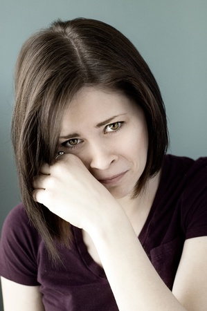 A portrait of a sad young woman crying and wiping her eyes.