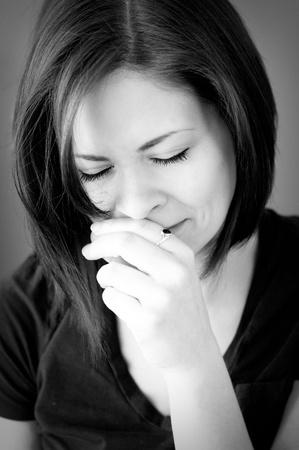 donna che grida: Un ritratto di una giovane donna triste piangendo con gli occhi chiusi in bianco e nero.