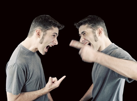 A young man in an argument with himself - concept of inner struggle. Stock Photo