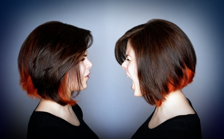 herself: A young woman in a fight with herself - inner struggle. Stock Photo