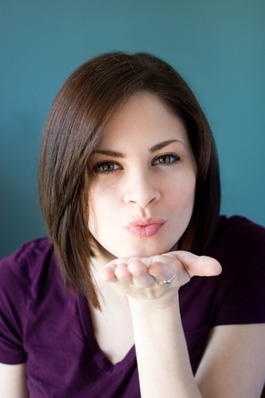 A young woman blowing a kiss straight at the camera.