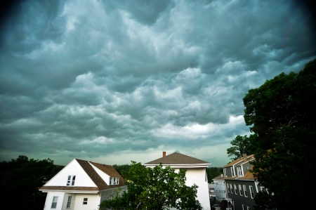 Some ominous storm clouds in the sky over houses in a neighborhood  Stock fotó
