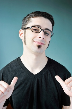 A young man pointing at himself with both thumbs. Stock Photo