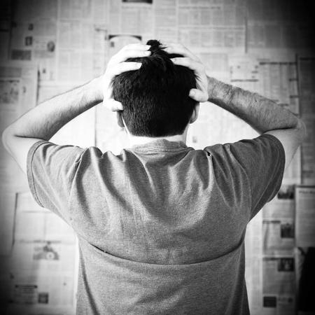 hombre preocupado: Hombre joven abrumado por las malas noticias con las manos en la cabeza en peligro.