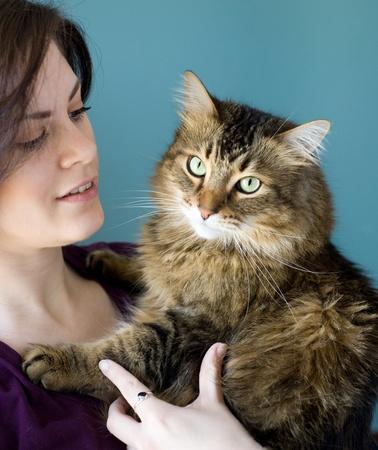 maine coon: Eine junge Frau mit ihrem Haustier Maine Coon Katze.