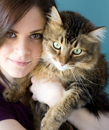 maine cat: A young woman holding her pet Maine Coon cat.