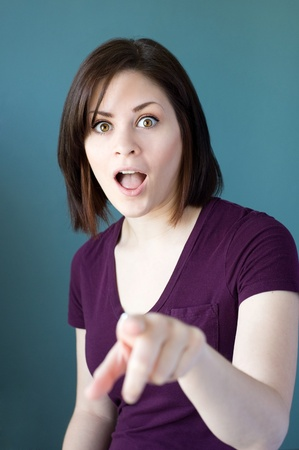 A portrait of a shocked young woman with wide eyes pointing at you.