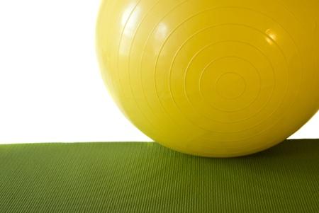 A yellow exercise ball on a green exerciseyogapilates mat. Isolated on white